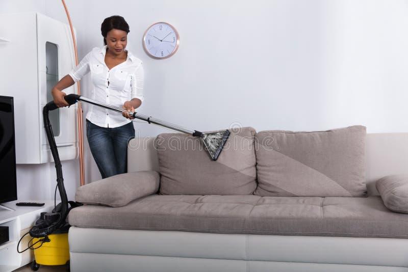 Afrykańska kobiety Cleaning kanapa Z Próżniowym Cleaner zdjęcia stock