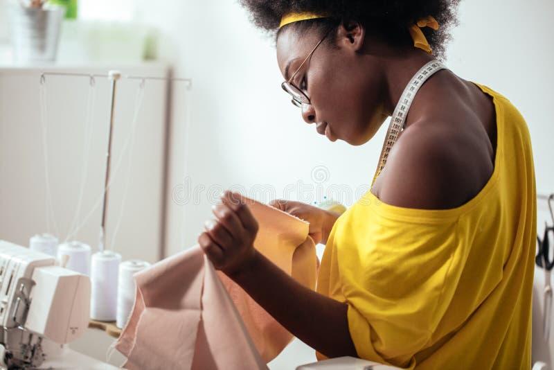 Afrykańska kobiety szwaczka patrzeje różowe tkaniny i pozycję w warsztacie obraz stock