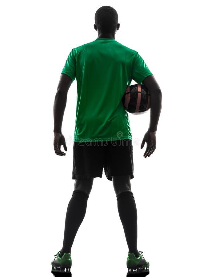 Afrykańska mężczyzna gracza piłki nożnej mienia futbolu sylwetka zdjęcia royalty free
