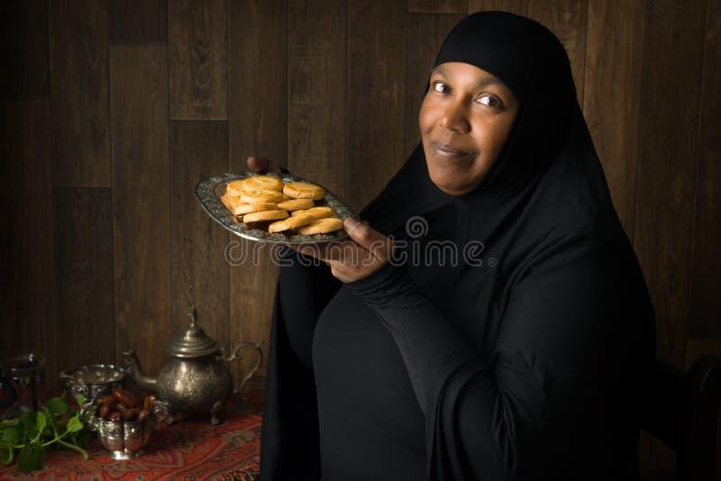 Afrykańska muzułmańska kobieta przedstawia ciastka zdjęcia royalty free