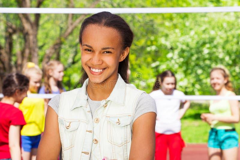 Afrykańska nastoletnia dziewczyna i przyjaciele bawić się siatkówkę zdjęcia stock