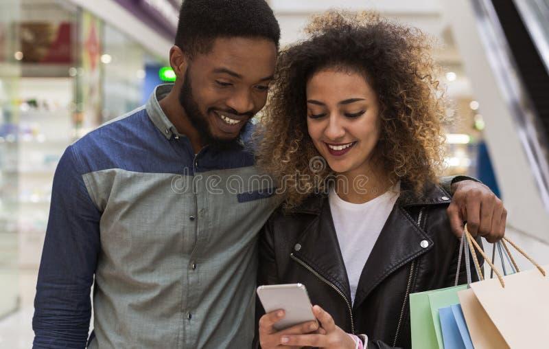 Afrykańska para z telefonów komórkowych zapraszającymi przyjaciółmi centrum handlowe obrazy stock