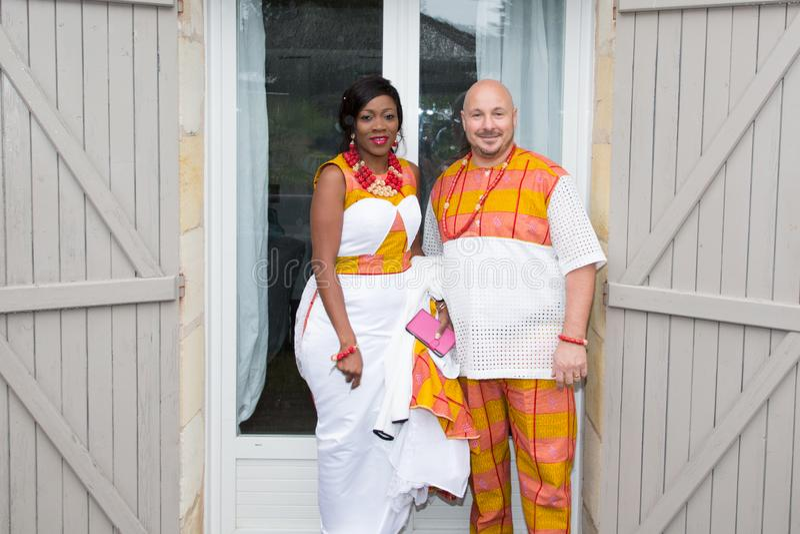 Afrykańska rodzina w jaskrawy etnicznym odziewa przed domem dla poślubiać mieszającego biegowego międzyrasowego amerykanina obraz royalty free