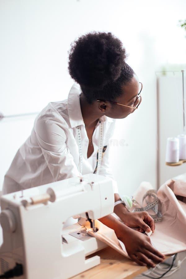 Afrykańska szwaczka pracuje z tkaniną bierze miary fotografia royalty free