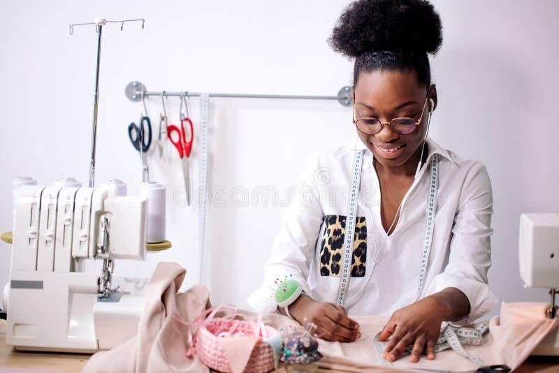 Afrykańska szwaczka pracuje z tkaniną bierze miary zdjęcia stock