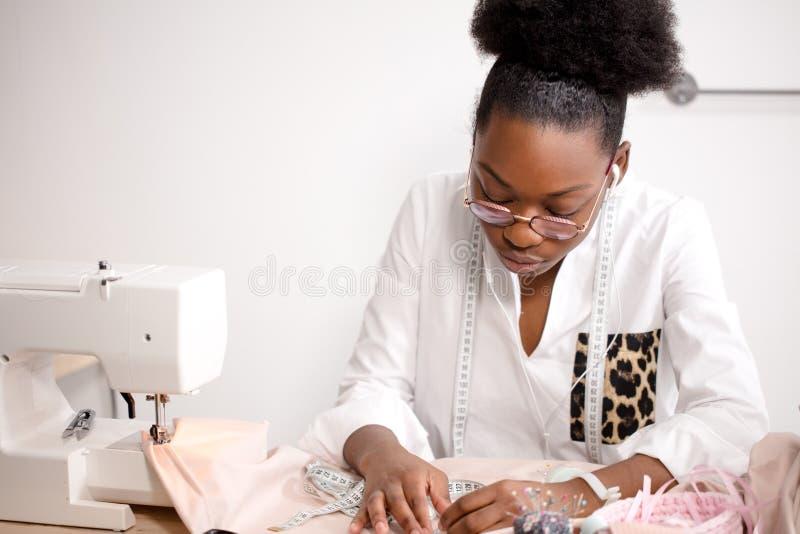 Afrykańska szwaczka pracuje z tkaniną bierze miary zdjęcie royalty free