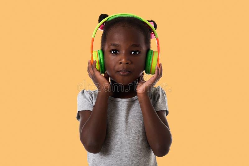 Afrykańska urocza mała dziewczynka z hełmofonami zdjęcia stock