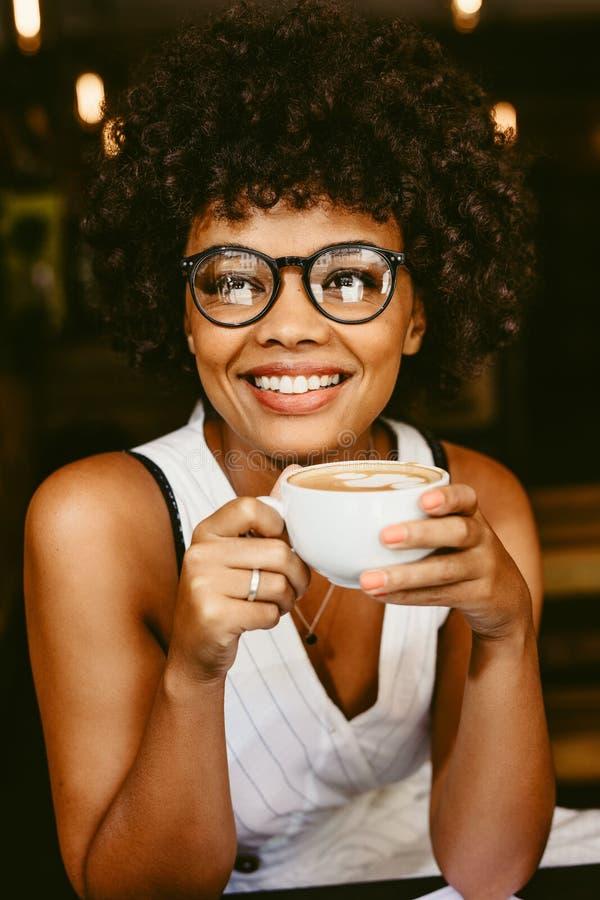 Afrykański żeński mieć kawę przy kawiarnią obrazy stock