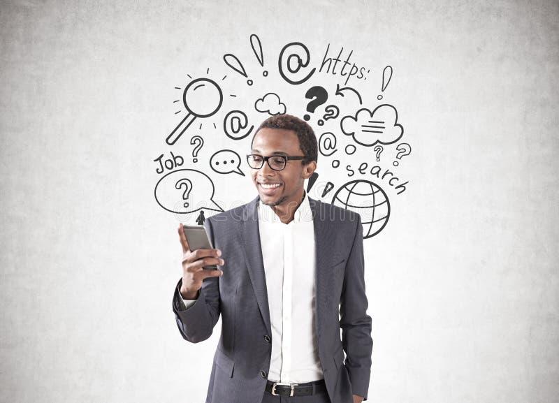 Afrykański biznesmen, smartphone, internet rewizja zdjęcie royalty free