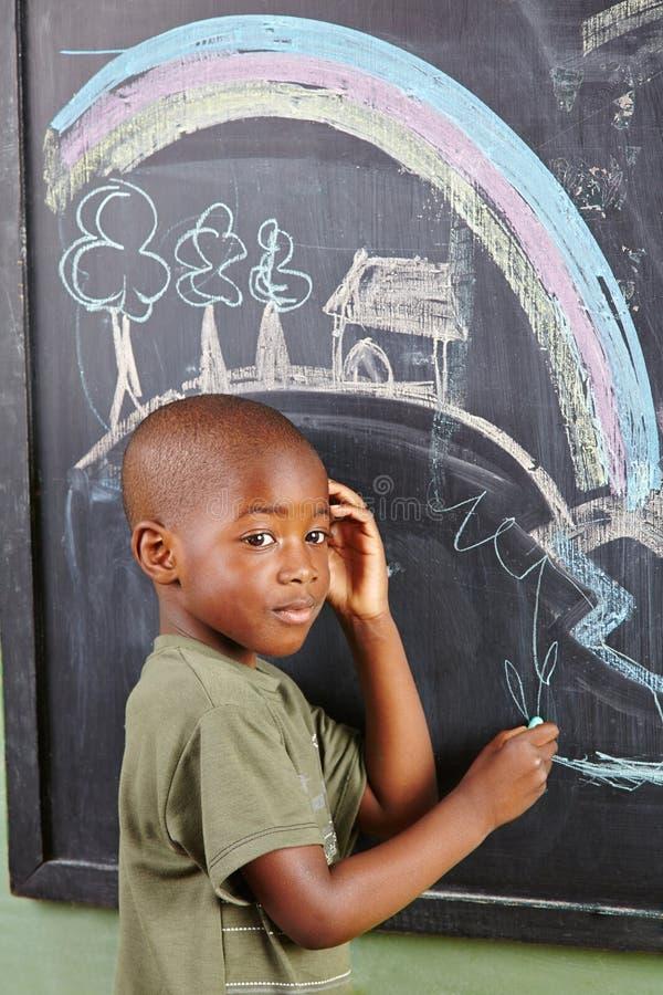 Afrykański chłopiec rysunek na blackboard fotografia stock