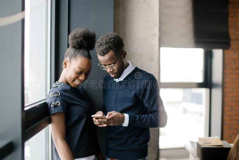 Afrykański facet pokazuje coś ciekawi jego czarny kolega w telefonie komórkowym zdjęcie stock