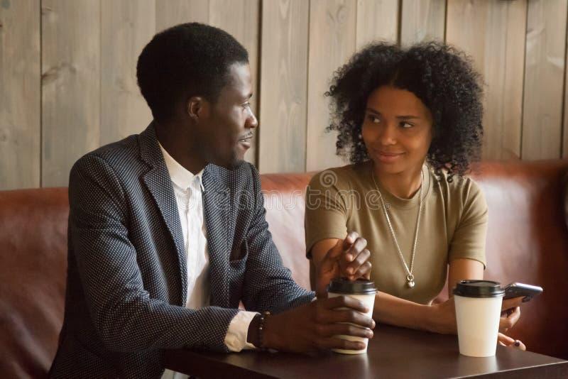 Afrykański mężczyzna i kobieta opowiada flirtujący siedzieć przy coffeehouse ta obraz royalty free
