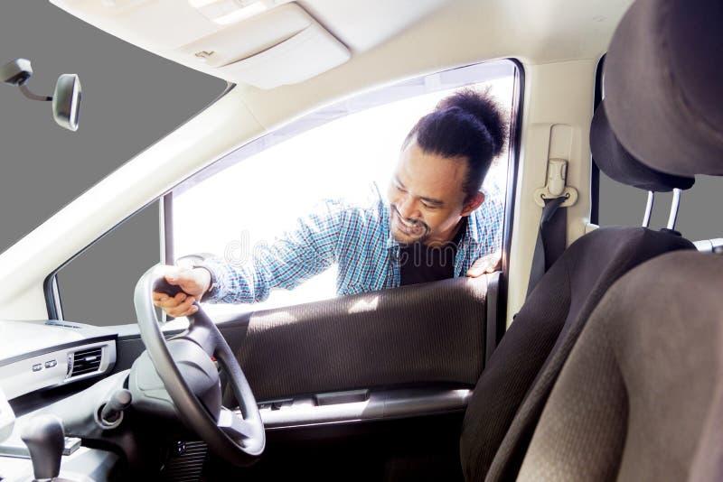 Afrykański mężczyzna podziwia jego nową kierownicę obraz stock