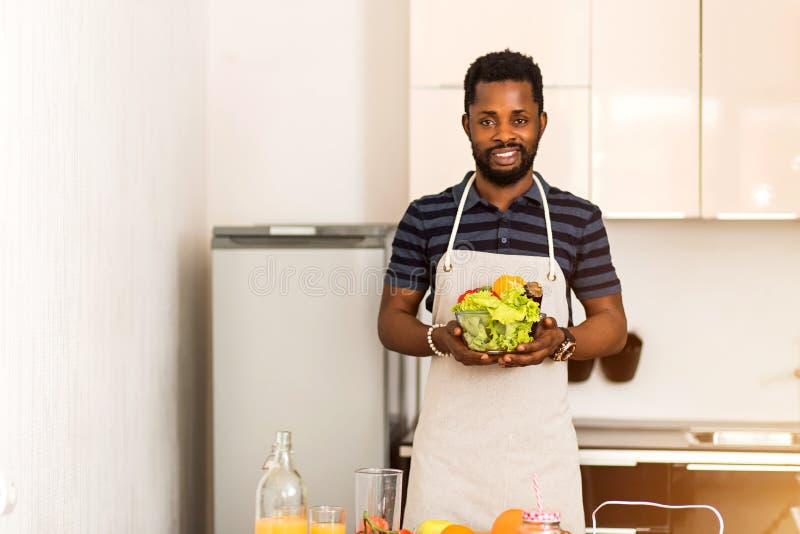 Afrykański mężczyzna przygotowywa zdrowego jedzenie w kuchni w domu fotografia royalty free