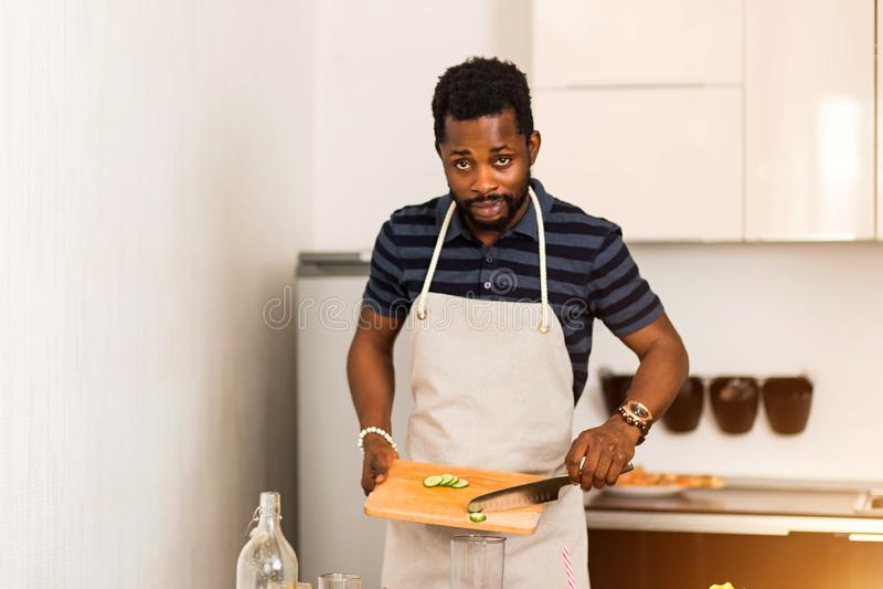 Afrykański mężczyzna przygotowywa zdrowego jedzenie w kuchni w domu fotografia stock