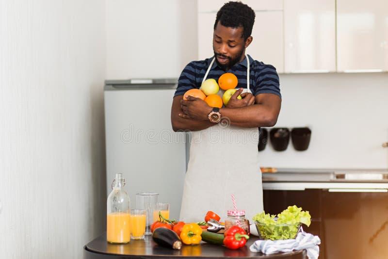 Afrykański mężczyzna przygotowywa zdrowego jedzenie w kuchni w domu zdjęcie stock