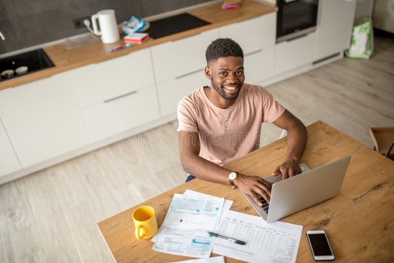 Afrykański mężczyzna używa laptop przy kuchnią podczas gdy caucasian dziewczyny stać osamotniony fotografia stock
