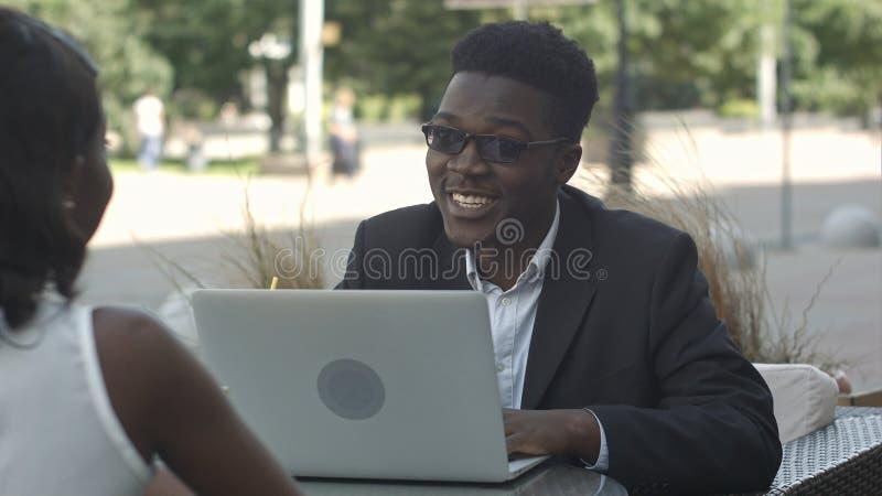 Afrykański mężczyzna wyjaśnia strategię biznesową jego afrykański żeński kolega, używać laptop podczas spotkania przy kawiarnią obrazy stock