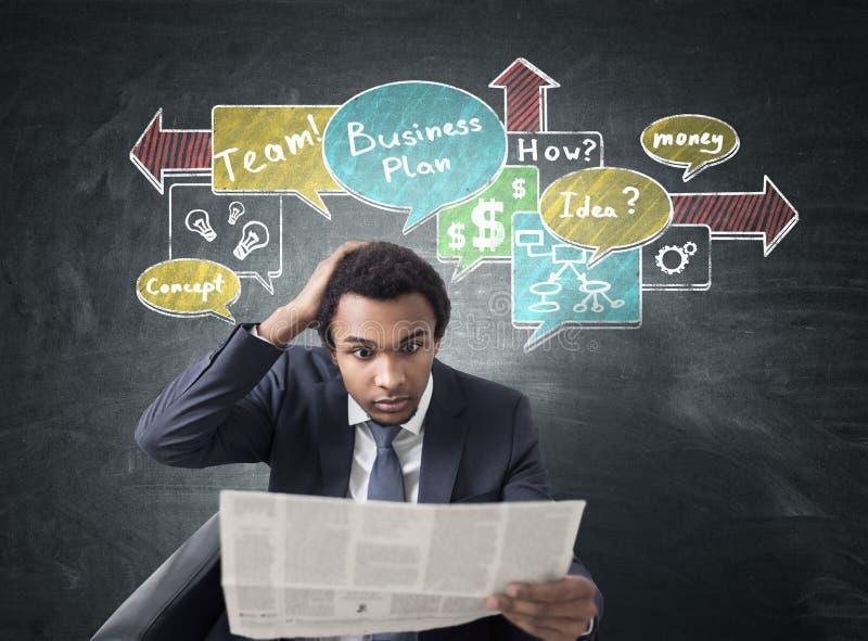 Afrykański mężczyzna z gazetą i planem biznesowym obraz stock