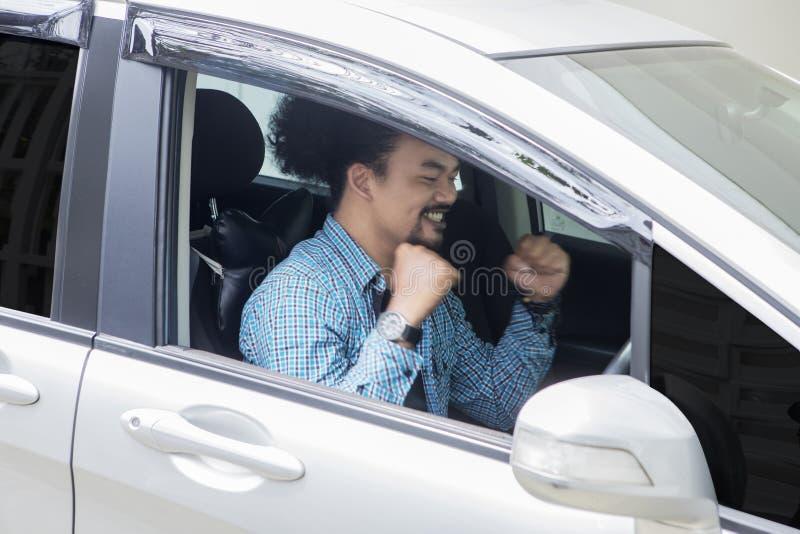 Afrykański mężczyzny wyrażać szczęśliwy w jego nowym samochodzie obraz stock