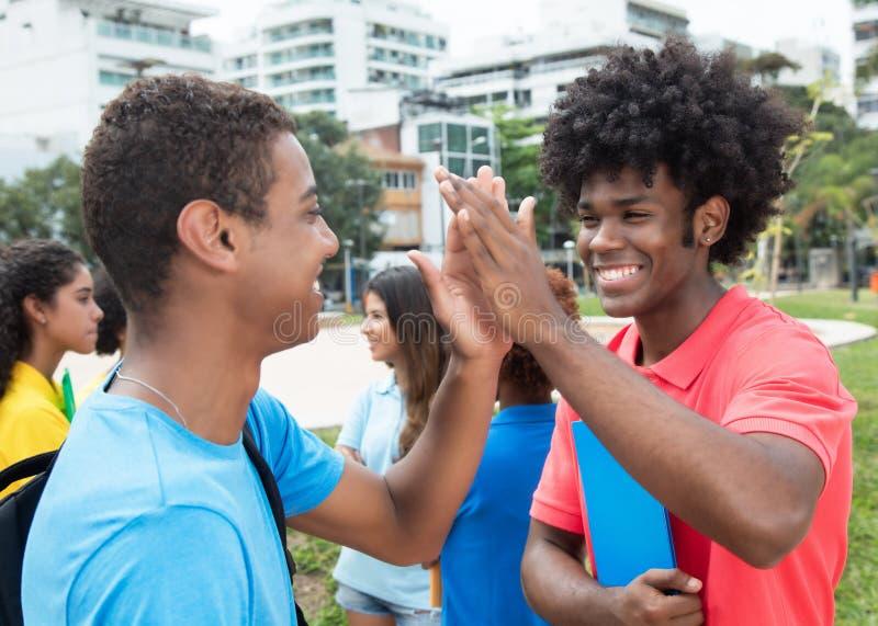 Afrykański męski uczeń daje wysokości pięć indyjski uczeń fotografia royalty free