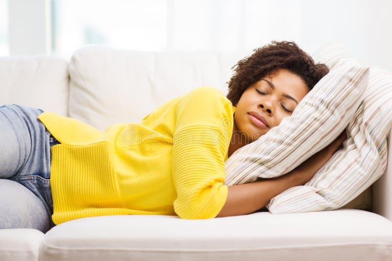 Afrykański młodej kobiety dosypianie na kanapie w domu obraz royalty free
