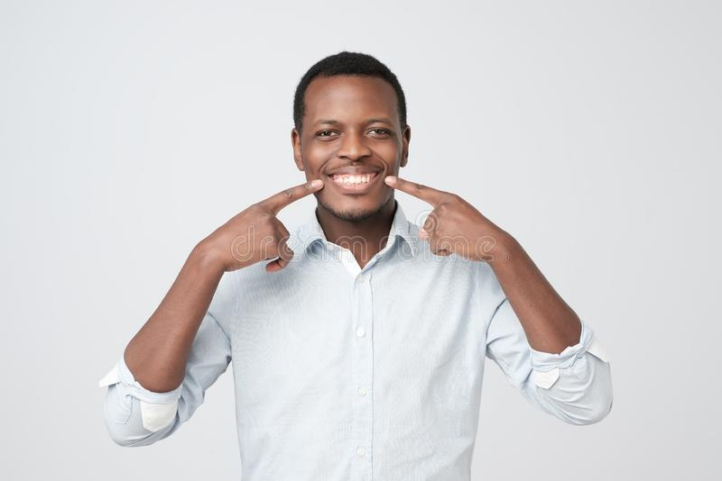 Afrykański młody przystojny mężczyzna pokazuje jego znakomitych białych zęby zdjęcia royalty free