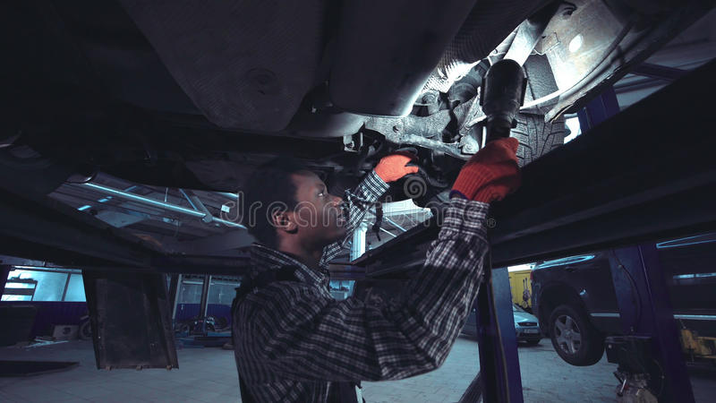 Afrykański mechanik pracuje na spodzie samochód obraz royalty free