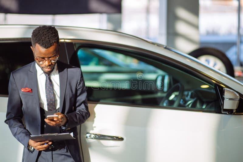 Afrykański samochodowy sprzedawca używa mądrze telefon w sala wystawowej zdjęcia royalty free