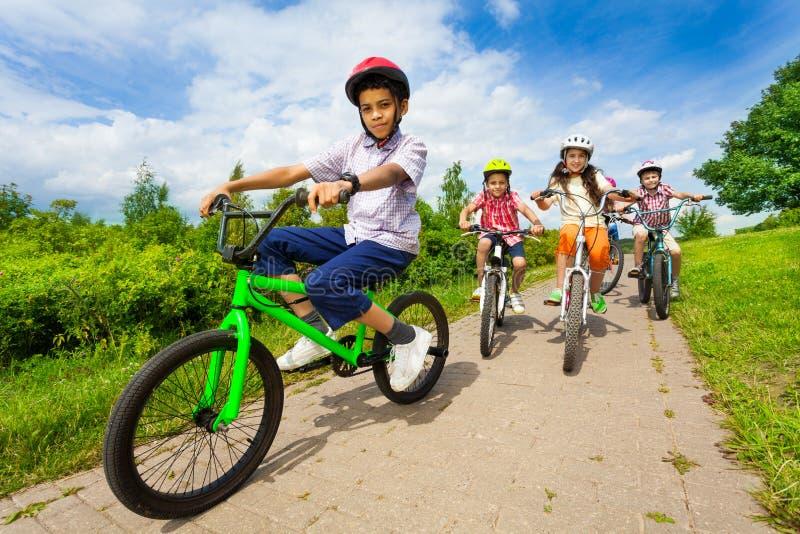 Afrykańskie facet przejażdżki jechać na rowerze z przyjaciółmi jedzie behind fotografia stock