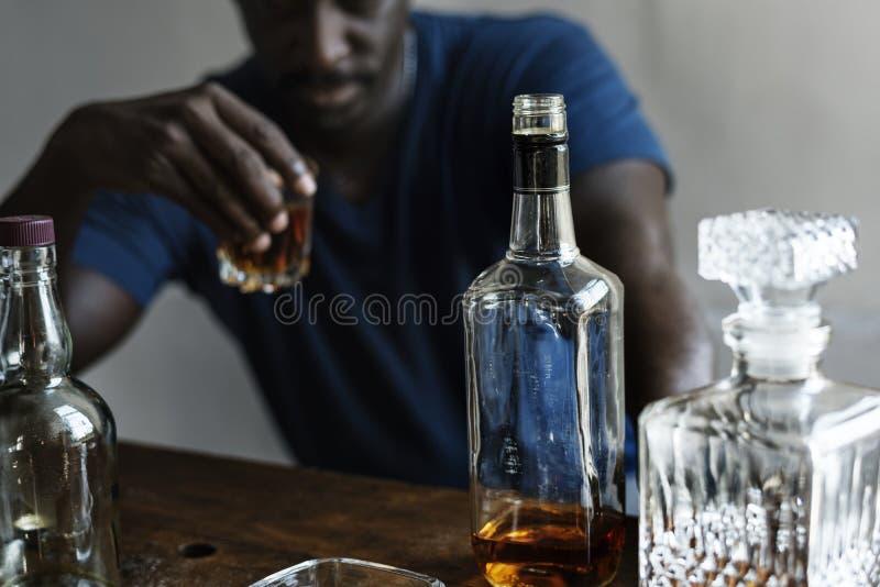 Afrykańskie pochodzenie mężczyzna obsiadanie pije whisky alkoholicznego nałogu złego przyzwyczajenie obraz stock