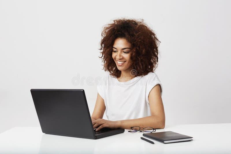 Afrykańskiego bizneswomanu uśmiechnięty działanie przy laptopem nad białym tłem zdjęcie royalty free