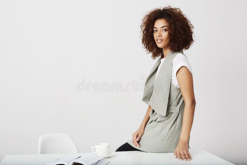Afrykańskiego bizneswomanu uśmiechnięty obsiadanie na stole przy miejscem pracy nad białym tłem zdjęcie royalty free