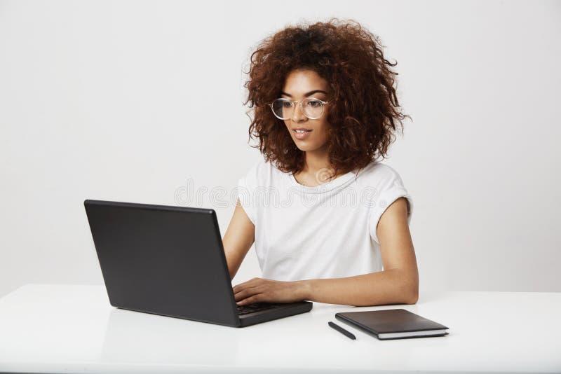 Afrykańskiej biznesowej damy uśmiechnięty działanie przy laptopem nad białym tłem zdjęcie royalty free