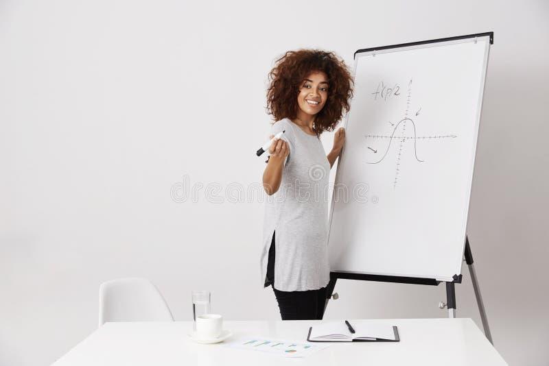 Afrykańskiej dziewczyny markiera uśmiechnięty trwanie pobliski whiteboard nad białym tłem zdjęcia stock
