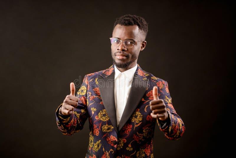 Afrykanin ubierał wykonawcy thumbing w górę odosobnionego na czarnym tle obraz stock