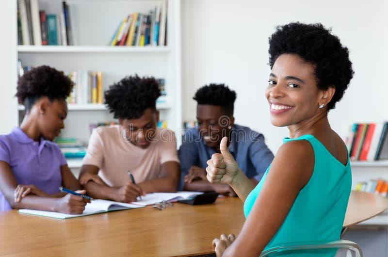 Afrykanina dojrzały adiunkt z uczniami przy pracą zdjęcie stock