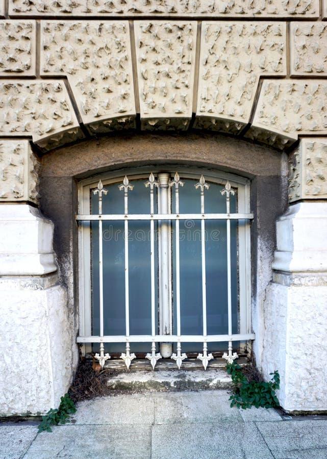 Afscheidingvoorgevel met oud geruïneerd venster met decoratieve metaalnetten stock afbeeldingen