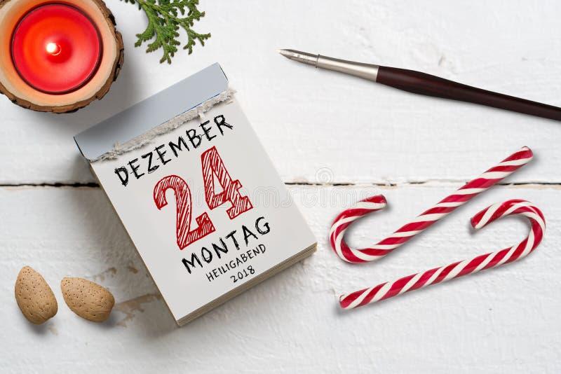 Afscheuringskalender met 24 van december in het Duits op bovenkant op een houten oppervlakte stock afbeeldingen