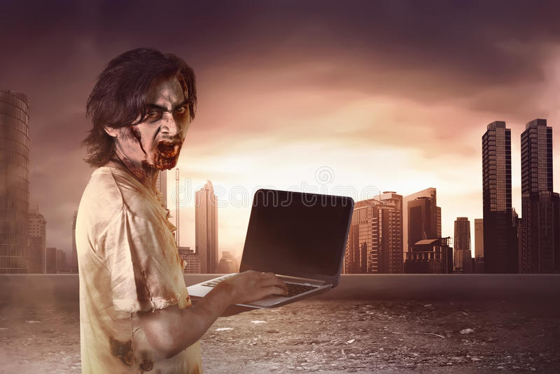 Afschuwelijke mannelijke zombieën die zich het typen in laptop bevinden die behin bekijken royalty-vrije stock foto's