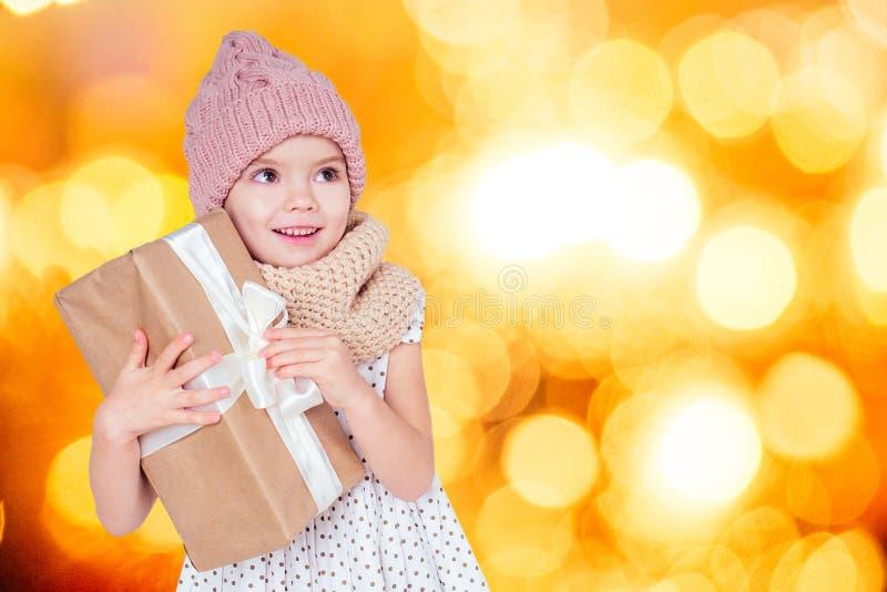 Afsluitend portret van een klein gelukkig en mooi blond meisje in een jurk, hoed en breidoek die in de handdoos zit met stock fotografie