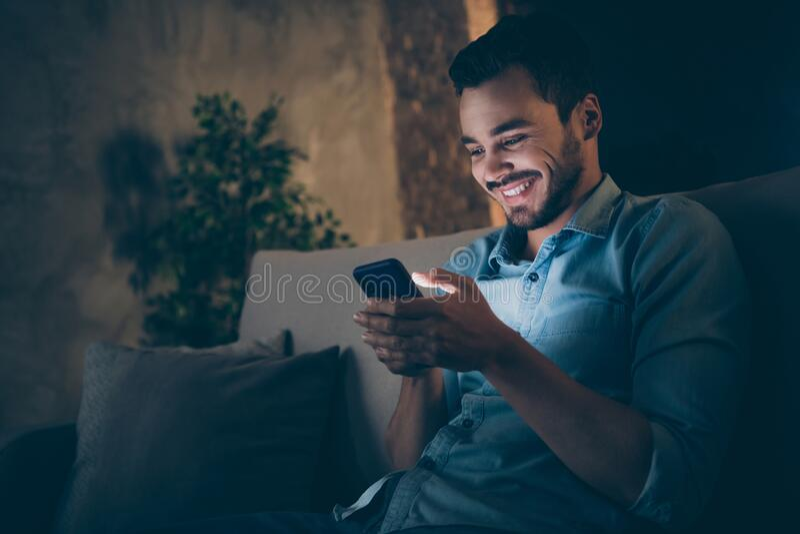 Afsluitend portret van zijn mooie, vrolijke, vrolijke brunet-man die op divan zit met het internet van mobiel surfen stock afbeeldingen