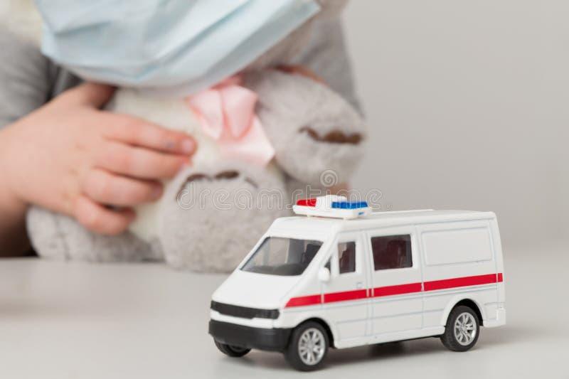 Afsluiting van het speelgoed van de ambulance op het bureau en het kind achter het bureau royalty-vrije stock foto