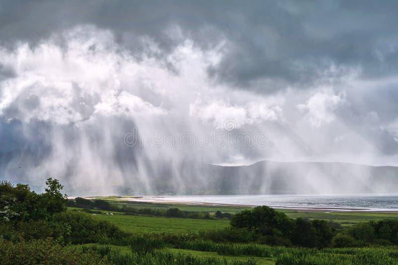 Afstandsmening van een regenonweer Gietend onderaan water over bergen, zonstralen, strand Ring van Kerry, Ierland stock foto's