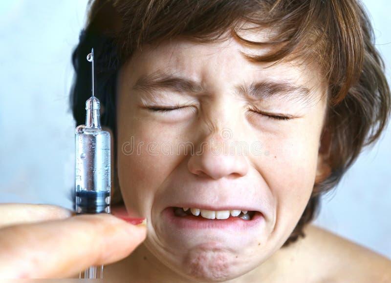 Aftaid del ragazzo dell'iniezione di vaccinazione fotografia stock