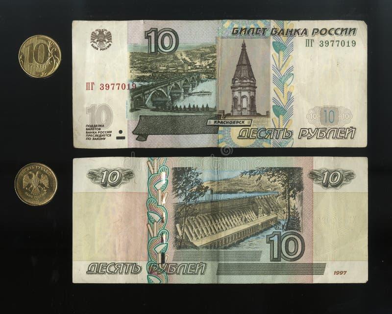 Aftasten Russische bankbiljetten en muntstukken, de obvers en het omgekeerde van nominale waarde van tien roebels Op een zwarte a stock afbeeldingen