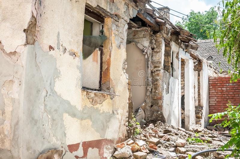 Aftermath catastrophe after hurricane or war disaster damaged and ruined house property with bricks and cracked plaster.  royalty free stock photos