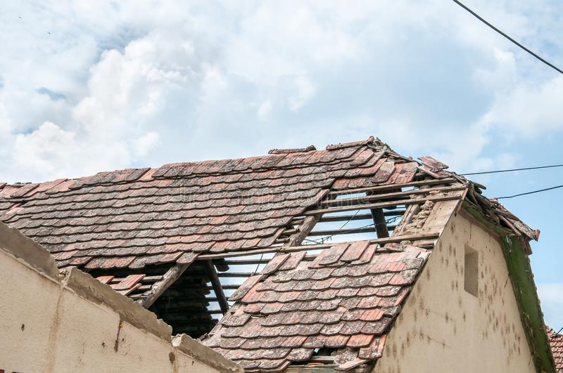 Aftermath damaged and collapsed roof on ruined house with wooden construction frame and brick wall stock photos