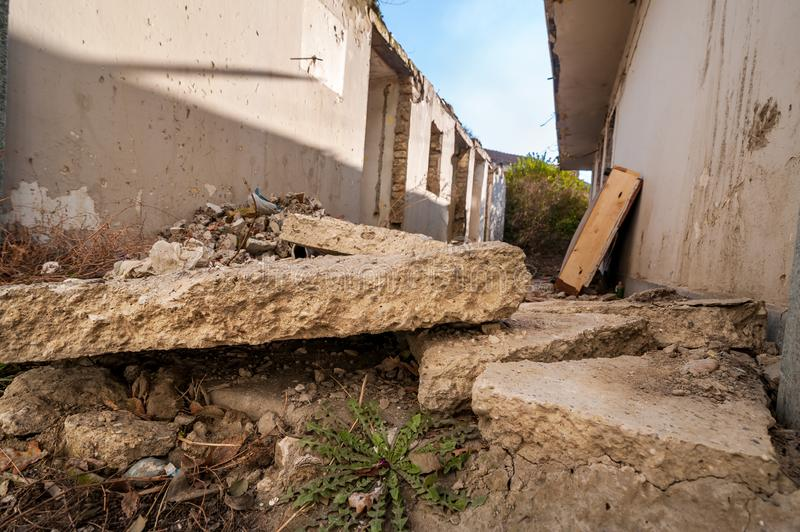 Aftermath remains of hurricane or earthquake disaster damage on ruined old house with collapsed roof and brick walls selective foc. Us low point of view royalty free stock images