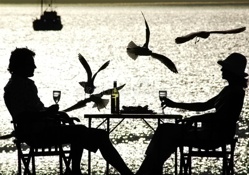 Couple having a meal by the sea. Silhouetted couple having a meal by the sea with flying seagulls and fishing boat in the background
